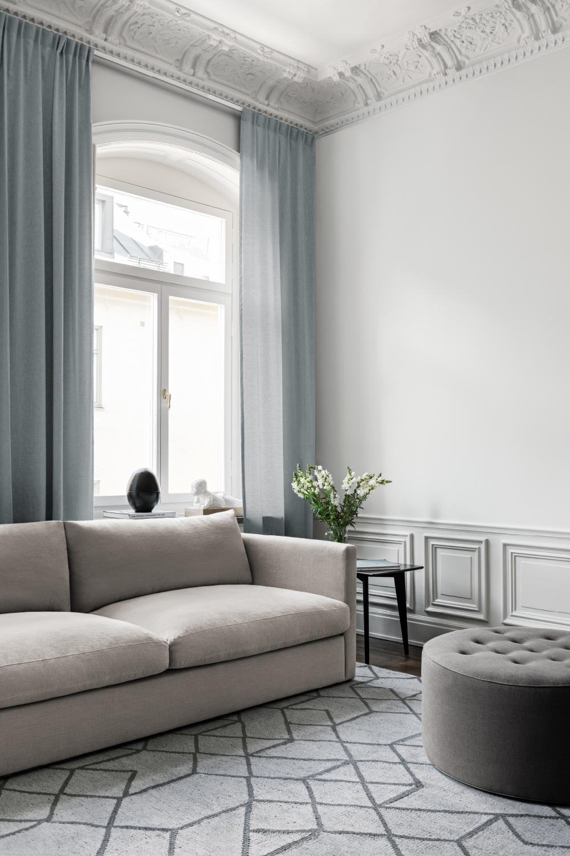 Elegant modern beige grå linnesoffa och mönstrad matta i vardagsrum från Layered