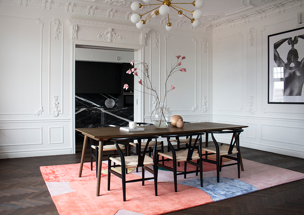 Layered Poppykalas colorful wool rug in dining room